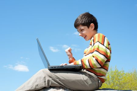 A shouting boy is sitting on the rock outside and playing a computer game photo