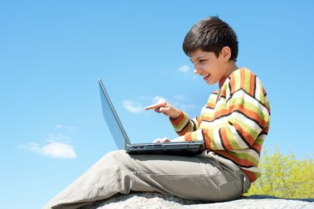 A kid is studying holding a laptop on his knees in front of the blue sky photo
