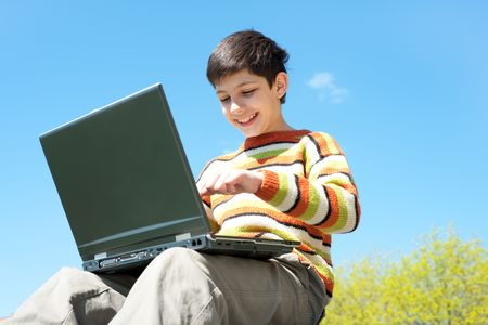 A handsome boy is studying holding a laptop on his knees in front of the blue sky photo