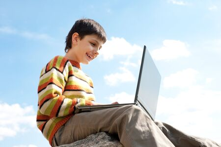 A smiling boy is studying holding a laptop on his knees in front of the blue sky photo
