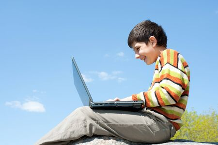 A laughing boy is studying holding a laptop on his knees in front of the blue sky photo