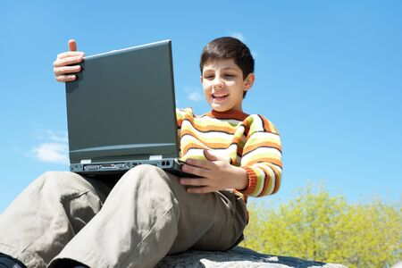 A happy boy is studying holding a laptop on his knees in front of the blue sky photo