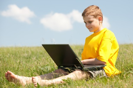 A smart boy with a laptop is sitting on the grass Stock Photo - 6927417