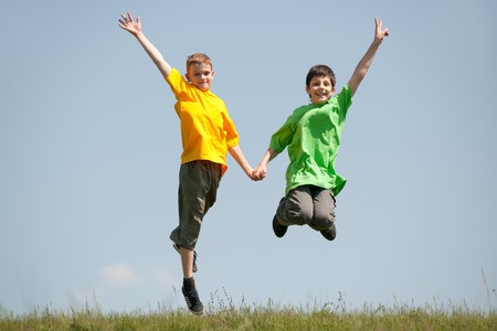 Two happy boys are jumping on the meadow photo