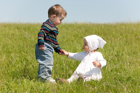 two boys: A toddler boy helps a toddler girl to get up in the meadow