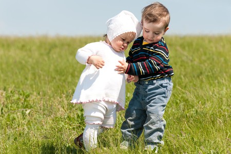 Two toddlers are walking on the meadow photo