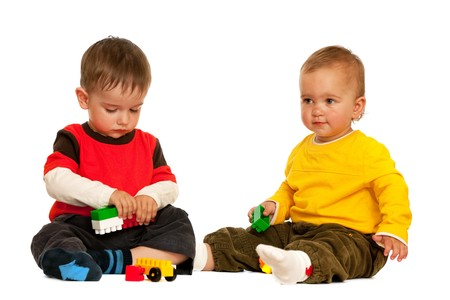 Two toddlers are playing with blocks; isolated on the white background photo