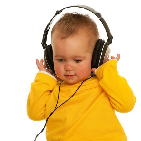 A little girl is wearing headphones; isolated on the white background photo