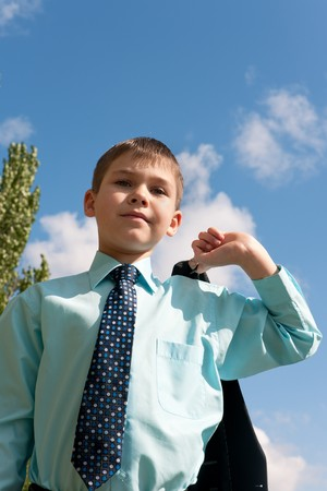fastens: A serious boy in tie is fastening his jacket