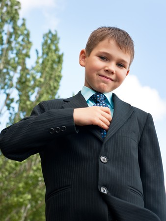 fastens: A smiling boy in black suit is checking his tie Stock Photo