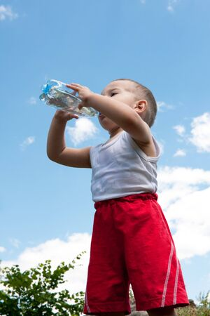 A little  boy is drinking whater outdoors against the sky photo