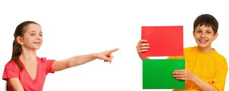 verschillen: Een lachende meisje wijst op een vel papier rode, welke het houden van een jongen; geïsoleerd op de witte achtergrond Stockfoto