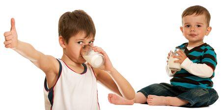 tomando leche: Dos hijos son beber leche; aislaron en el fondo blanco  Foto de archivo