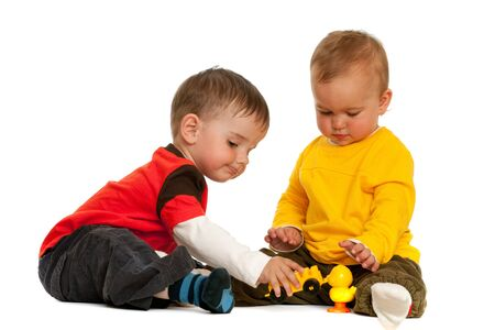 jardin infantil: Dos ni�os est�n jugando con bloques; aislaron en el fondo blanco