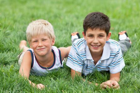 Two friendly handsome boys are lying on the grass photo