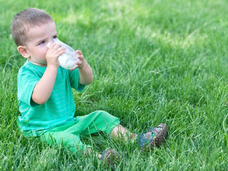 field stripped: A little boy in green is drinking milk sitting on the green grass