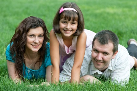 Father, mother and their daughter are lying on the green grass Stock Photo - 7632403