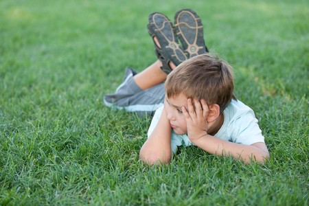 A  thoughtful boy is lying on the green grass photo