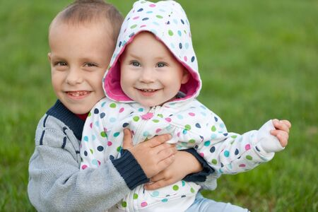 A smiling brother is sitting on the green grass and hugging his little siister Stock Photo - 7809705
