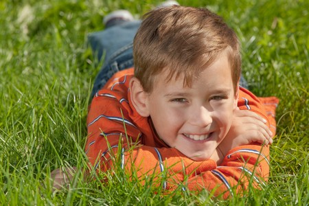 A handsome smiling boy is smiling lying on the green meadow Stock Photo