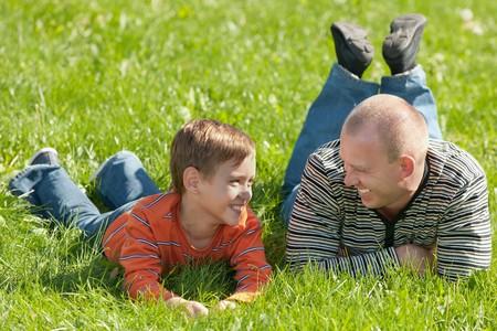 Een vader en zijn zoon praten en lachen terwijl ze rusten in het zomerpark Stockfoto