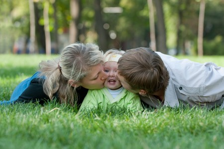Father and mother are kissing their daughter from both sides Stock Photo - 7877801