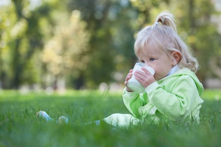 A serious toddler is drinking milk from a glass sitting on the grass photo