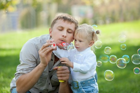 blowing bubbles: A dad and his daughter are making bubbles in the park Stock Photo
