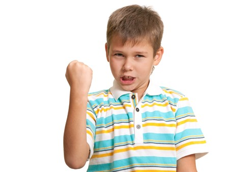 impulsive: An angry boy with a risen fist is yelling; isolated on the white background