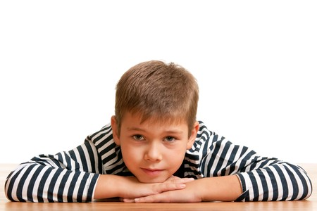 A handsome thoughtful kid is lying on the wooden background with his head on his hands photo