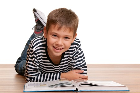 A handsome smiling kid is reading a thick book lying on the wooden background; isolated on white photo