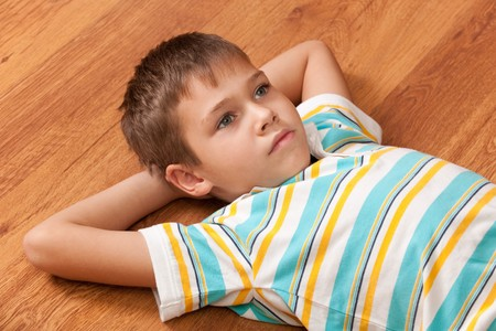 A handsome thoughtful kid is lying on the wooden background photo