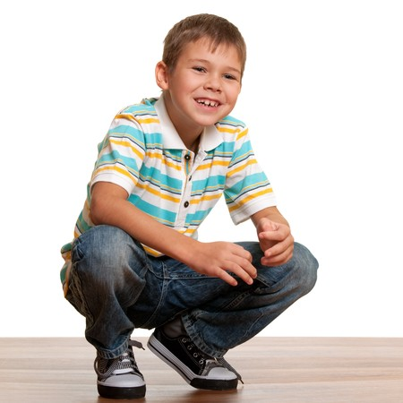 squat: A handsome smiling blond kid in casual clothes squats above the wooden background; isolated on white