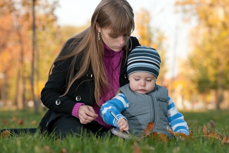 A mother is teaching her little son to draw while walking in the autumn park photo