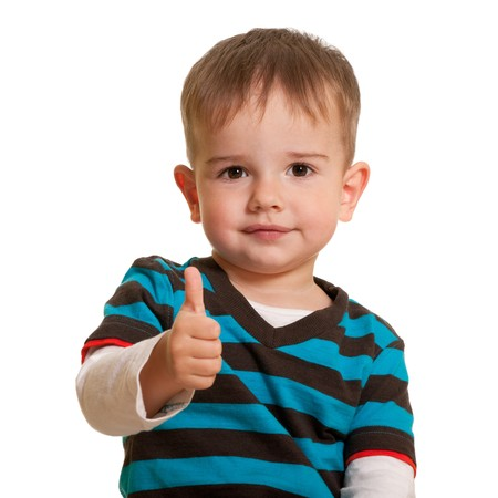A happy handsome kid is holding his thumb up; isolated on the white background photo