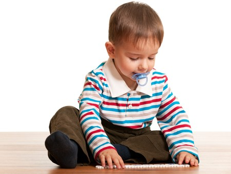 Lovely toddler trying to read letters on cards; isolated on the white background photo