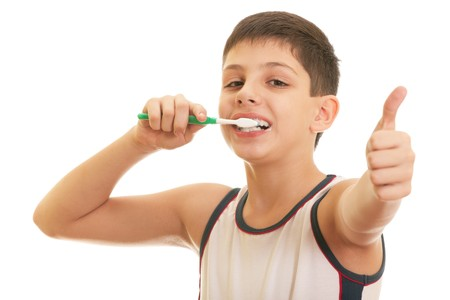 routine: A happy boy is brushing his teeth; isolated on the white background