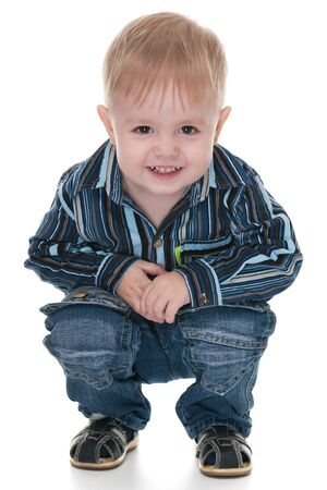 squat: A handsome smiling toddler squats; isolated on the white background Stock Photo