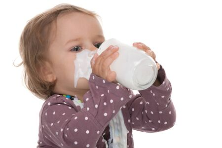A pretty little girl is drinking from a glass of milk having milk moustache; isolated on the white background photo