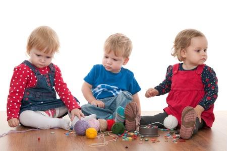 hermanos jugando: Tres de los ni�os peque�os est�n jugando con hilados y botones; aislado en el fondo blanco