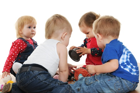Four toddlers are playing with yarn and buttons; isolated on the white background photo