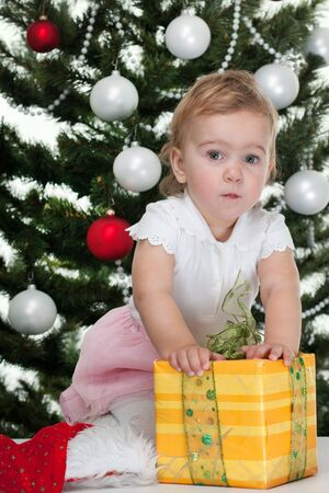A pretty girl with a christmas gift is standing at a new year tree photo
