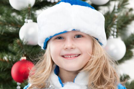 A pretty girl in a blue and white christmas hat is standing at a new year tree photo