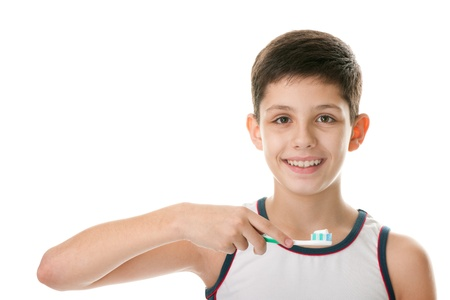 A handsome boy is brushing his teeth; isolated on the white background photo