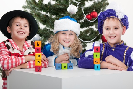 Three children dressed in carnival suits are greeting with sigh happy new year made with blocks at the decorated christmas tree; isolated on the white background photo