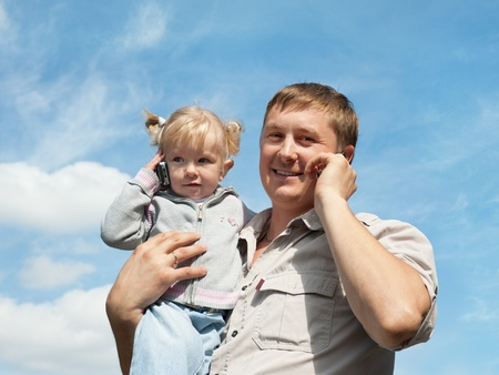 A father is holding his daughter infront of blue sky; both are talking on the mobile phones photo