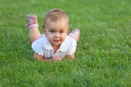 A cute little girl is lying on the green grass in the park photo
