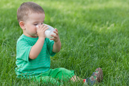 A little toddler in green is drinking milk from a glass sitting on the green grass in the park photo