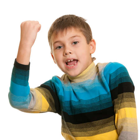 A happy kid is holding his fist up symbolizing a victory photo
