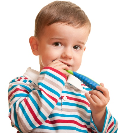 A toddler is brushing his teeth; isolated on the white background   photo